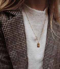 Gold pendant necklace with sweater and plaid blazer