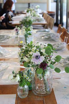 テーブルアレンジにはメイソンジャーなど、大きさの違うガラスボトルをランダムに並べています。 マトリカリアやアネモネハーブをたっぷり使って、庭から摘んできたようなナチュラルなガーデンウェディングのイメージに。 garden wedding,centerpiece,natural,green, matricaria,anemone,herb,glass,bottles