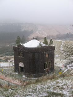 Abandoned building below dam of Lower Neuadd Reservoir - note trees growing from roof. In the mist, are the slopes of Craig Fan Ddu. In Powys, Great Britain.