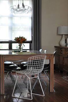 I am all over this. four black chairs, the 2 white accent bertoia chairs, the white lamp, the pile of bulbs as the chandelier. LOVE IT ALL!!