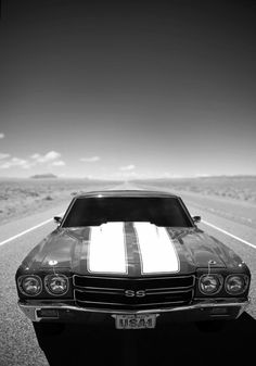 Vintage Chevrolet Chevelle on an open road through the desert. Black with white stripes and USA-1 license plate.