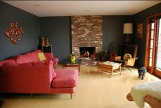 Mid century modern living room dark grey with brick fireplace and coral sofa