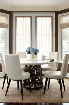dining rooms - chocolate brown walls French doors bamboo roman shades sisal rug round marble top dining table ivory leather contemporary dining chairs