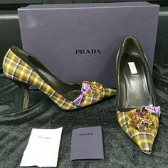 Flash sale!  Prada plaid pumps Turn heads in these stunning plaid pumps! Bronze studded curved heel,  brown green blue & black plaid fabric with a cute purple bow and jeweled toe. Comes with box, additional taps and care card. Flawless condition except wear on the soles. Prada Shoes Heels