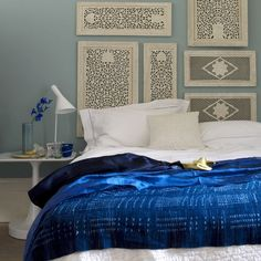 Decorative wooden shutters replace a headboard, while a shibori throw creates a colorful focal point.