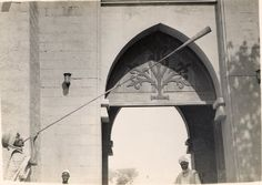 """Nigeria, adult male blowing long wind-instrument in front of gate with pointed arch. """"Announcing the Civic Court outside the Emir of Kano's Palace"""". Two other male adults in front of gate, males wearing robes and head-gear. Outdoor setting. Medium: Gelatin silver print."""