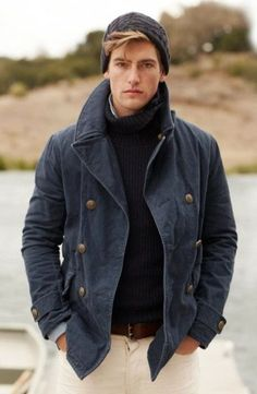dark knit hat, navy canvas pea coat, navy roll neck sweater, light blue shirt, brown belt, white pant