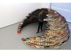 """home"" by columbian artist miler lagos is a seven foot tall igloo-shaped sculpture made out of books. the sculpture was on display last fall at the magnanmetz gallery in new york city."
