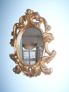 Hand carved wooden mirror frame with gold leaf.