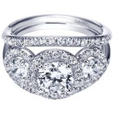 The center diamond in this white gold engagement ring has a single diamond on each side. A stunning round halo outlines each of these diamonds while pave set diamonds flow down to accent the split shank band at 1 carat total weight. Halo Diamond Engagement Ring, Engagement Rings, Three Stone Rings, Anniversary Rings, White Gold Diamonds, Wedding Rings, Bling, Jewels, Gemstones
