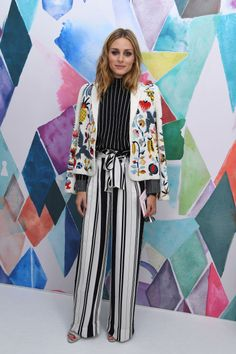 Olivia Palermo wearing a black and white striped turtle neck and parachute pants, as well as a beaded and embroidered creme jacket at the Schiaparelli show at Paris Couture Week.