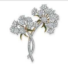 TIFFANY & CO | DIAMOND AND TSAVORITE GARNET BROOCH  Designed as two circular-cut diamond Queen Anne's Lace flower blossoms brooch | tsavorite garnet leaves, with diamond blooms and stems, set in gold and platinum.  Signed.