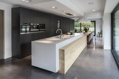 Large island with wood feature which runs the entire length. Cleverly integrates dinning space with kitchen island. Culimaat Ligna design keuken #keuken #design