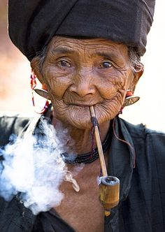 Woman of the Ann tribe in traditional black dress smoking a pipe outside a hill village near Kengtung (Kyaingtong), Shan State, Myanmar (Burma)