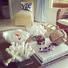 Lots of HomeGoods goodness here: faux coral, rope knot door stop (similar here), barnacle, shell bowl, candle, driftwood ball, blue & white seaweed pillow, large woven tray basket.