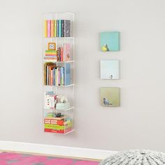 Consider this acrylic bookcase to hang to the left of the windows for some book and toy storage without taking up any floor space. Also, since it's acrylic, it won't take up much space visually and will help the room seem roomier.