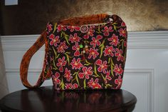 """It's time for a """"Garden Party!""""  This cross body bag features a gorgeous Spring print in brown, red, green and orange.  A wooden and glass beaded tassel hangs down the front, and a cell phone pocket is conveniently located on the strap.  Want to see more pictures?  Check out my other designs on Facebook at Bobbin My Thread!"""
