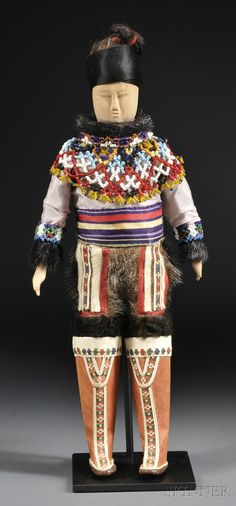 Greenland Eskimo Carved Wood Male Doll, c. second quarter 20th century, dressed in traditional clothing with inlaid hide mukluks and elaborate beaded collar, with stand, ht. 14 in.