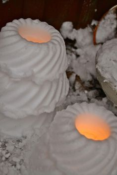 Pack snow into cake molds, then tap to slide out. Place tea candles in the middle. Gives off a welcoming, warm glow during the holidays when placed along the walkway or front steps to your home.