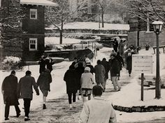 Athena yearbook, 1963. Students walk the snowy bricks towards the College Green. The corners of Ellis Hall are on the right and Boyd Hall (old) on the left, where Alden Library is now.  :: Ohio University Archives