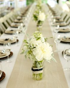 Glass jars filled with white flowers and greenery dotted the long tables.
