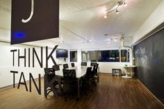 """The ThinkTANK: The ThinkTANK is an intimate, 350 square foot meeting space adjacent to the DreamBOX. Ideal for small gatherings, business meetings, brainstorm sessions and temporary creative space, the ThinkTANK has boardroom-style seating, 42 inch plasma screen TV, DVD player, complimentary Wi-Fi and an entire chalkboard wall for recording those """"Aha!"""" moments."""