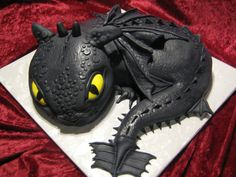 """Baby """"Toothless"""" Dragon ( How to train your dragon) - All cake, no Rice Crispy treats. Used Wilton's Oval pan for head and body, carved a little..Used carved pieces for the tail"""