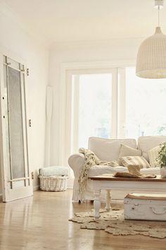 beachy decorating abeachcottage.com coastal vintage style white sofa, wicker pendant lamp, jute rug, vintage door, nautical stripe x