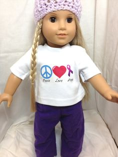 """White T-shirt with Peace Love Hope design. Peace sign is blue, heart is dark pink and the ribbon is purple. Pajama pants are dark purple and made from flannel material. Fits and 18"""" doll."""
