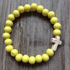 Armband van 8mm lemon yellow hout met witte howliet kruis. Van JuudsBoetiek, €3,50. Te bestellen op www.juudsboetiek.nl.