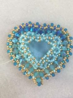 Bead Love: A beautifully encased and encrusted heart from Edgar Lopez. Could easily be reversed or worked without the central stitches for use as a frame or link Beaded Brooch, Beaded Necklace, Beaded Bracelets, Necklaces, Bead Embroidery Jewelry, Beaded Bracelet Patterns, Seed Bead Jewelry, Heart Jewelry, Engagement Ring Sizes