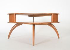 A 1940s Mid Century Modern Heywood Wakefield maple wood coffee table. A stylish piece with sensuous curves,  double tiered surface, raised on swooping legs. Makers mark to bottom. from EBTH.com