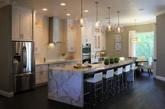 An extra-long island with waterfall countertop is the star of this family-friendly, contemporary kitchen. By removing a wall, the designer opened up this space to the family room beyond, creating an open floor plan that invites people to gather. Cabinetry extends to the ceiling and throughout the breakfast space, maximizing storage. The globe-style pendants are by Arteriors.