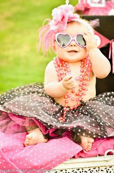 Letting her imagination run wild with her cute pearls and awesome heart sunglasses. Love it.