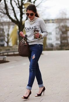 Grey paris sweater wth dark blue stylish jeans and brown leather hand bag and stylish high heels pumps