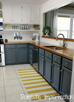 Stormy blue on lower cabinets and white on top, broken by butcher block counter tops.