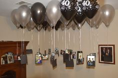 For my husband's 40th birthday I mounted pictures from his life onto black cardstock, hole punched them, and tied them to silver strings. Then I had the balloons filled with Helium and attached the balloons to my strings and pictures. We put 5 or so balloons in each corner of the house downstairs (30 altogether). Everyone loved looking at the pictures, they were great conversation starters, and they also were great decorations!