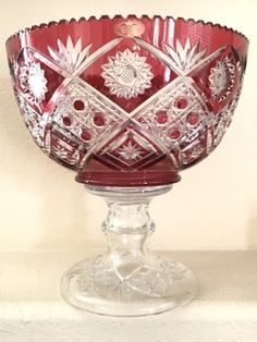 SCHONBORNER BLEIKRISTALL SIGNED CRANBERRY HAND CUT TO CLEAR CUT GLASS PEDESTAL BOWL WITH A DAISY BUTTON AND STAR PATTERN AND SAWTOOTH RIM. THIS EXCEPTIONAL PIECE MAKES FOR A GREAT CENTERPIECE WITH ITS LARGE SIZE AND COMMANDING PRESENCE. 12H X 12W