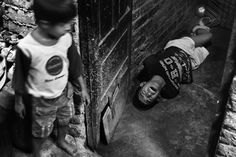 Wasim, 16, lies  on the floor of the family's living quarter, his hands and feet tied behind his back, while one of his younger brothers watches. His mother tied him up, with the help of a neighbor, after arguing about money for drugs. Wasim is the oldest of five children, living in one of the many slum settlements in Delhi.