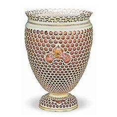Értékmentők - Gyugyi-gyűjtemény, Zsolnay kiállítás Pécsen  Talpas váza áttört szegéllyel  1888 A váza az ún. méhsejtes technikával készült, azaz a dupla falú edény elefántcsont színű külső köpenye hatszögletű méhsejt formában áttört. A dekort az edény belső köpenyére festették.