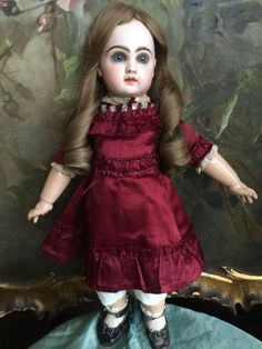 Very beautiful bebe Jumeau with no damages or repairs. Signed both head and body. She has cork pate long human hair wig Beautiful silk burgundy Dress