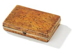 A Fabergé gold-mounted wood cigarette case, workmaster Victor Aarne, St Petersburg, 1899-1908, carved of Karelian birch, the chased bead and spindle rim mount with cabochon ruby thumbpiece.