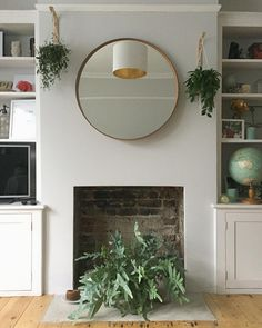 Grey walls, a round mirror and hanging plants. Above Fireplace Decor, Empty Fireplace Ideas, Round Hanging Mirror, Round Mirrors, Fireplace Mirror, Brick Fireplace, Wall Fires, Hanging Plant Wall, Chimney Breast