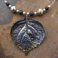 Necklace made with a porcelain hydrangea leaf and silver & onyx beads, one of a kind. Handmade in Switzerland.   www.ilemas.ch/en/