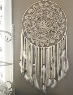 Shop Wild Cotton's giant dream catcher will make a statement in any boho inspired bedroom. This dream catcher is all natural colors with lots of natural feathers and stones.