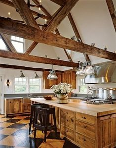"""The Cosays made few requests,"" the designer recalls. ""I pretty much had carte blanche on the entire project."" Says Healy Cosay, ""We could not have built a house 3,000 miles away without Karin."" To retrieve the old wood beams for the bright, spacious kitchen's ceiling, ""we hired a plane and flew up to New Hampshire,"" Cosay reports. Wolf range."