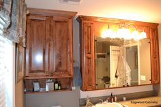 Combination mirror medicine cabinet and an over the toilet cabinet for extra storage.