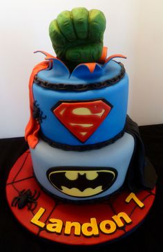 "Superheros Cake - A 7th birthday cake made for the son of a friend. The cakes were 9"" and 7"" rounds, covered with MFF. All decorations were handmade from fondant/gumpaste/RKT."