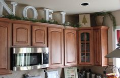 Big letters and pine garland above the kitchen cabinets..would be adorable for last name and keep up all year long!!