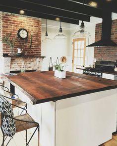Restored kitchen with brick fireplace, oak island countertop, black range hood, brick backsplash wall, wood beams, clear glass pendant lights